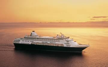 Sun setting over a cruise ship at sea